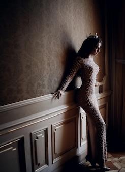 Привлекательная молодая девушка одета в бежевое вечернее платье у стены с идеальным телом