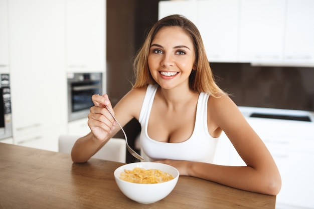 Привлекательная молодая девушка ест кукурузные хлопья с молоком улыбается