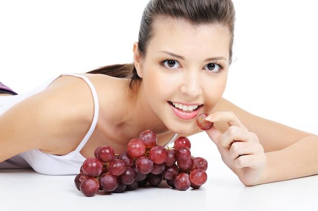Ragazza attraente che mangia uva - isolata su bianco