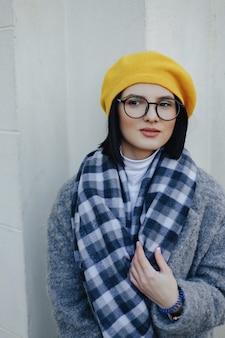 Attractive young girl in glasses in coat and yellow beret on a simple light background