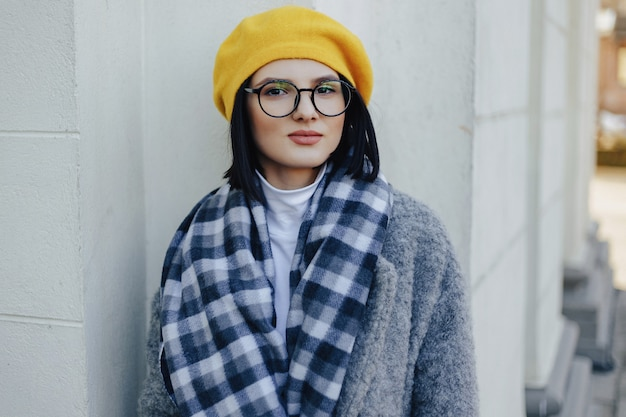 Attractive young girl in glasses in coat and yellow beret on a simple light surface