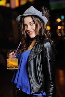 Attractive young girl in a gray bavarian hat drinks beer or a beer cocktail through a straw  of a ba