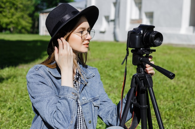 Attractive young girl in a hat makes photo on camera outdoors