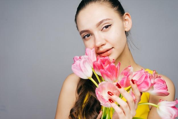 핑크 꽃 꽃다발을 들고 카메라를 보고 매력적인 젊은 여자