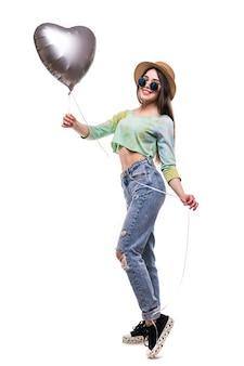 白で隔離されるバレンタインのヘリウム風船を保持している魅力的な若い女の子