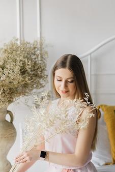 窓の近くの花と明るいドレスの魅力的な若い女の子