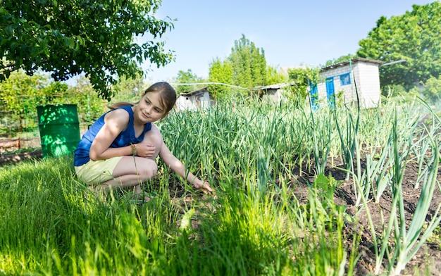 春の間に新しい若い植物をチェックして身をかがめる菜園の魅力的な若い女の子