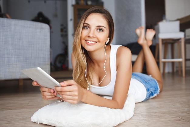 Привлекательная молодая девушка лежит на полу и держит планшет в руках в гостиной