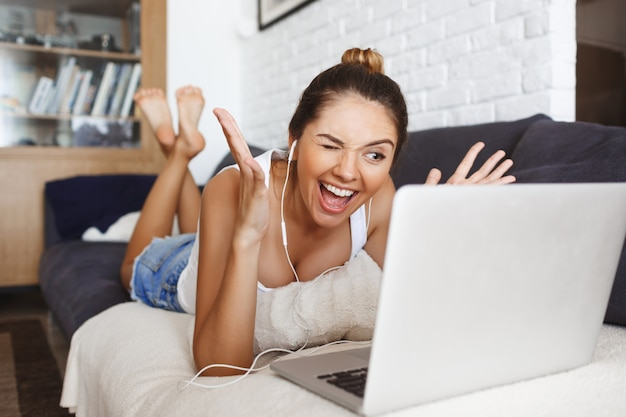 Attractive young girl laying on sofa at living room with laptop.