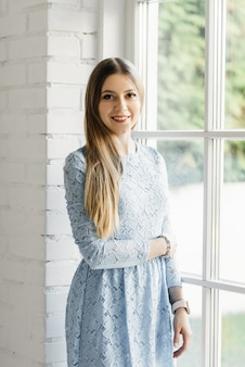 Attractive young girl near the window in a blue dress