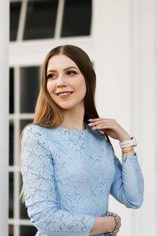 青いドレスを着た白い家の背景に魅力的な若い女の子