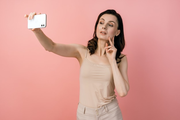 携帯電話で自分撮りショットを撮ってポーズをとる魅力的な若い女の子