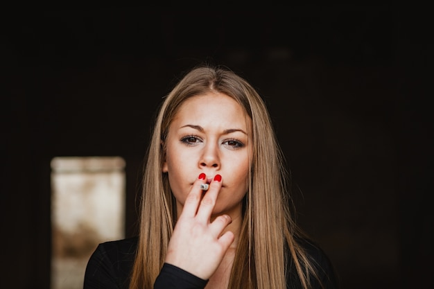 Attractive young girl smoking a cigar
