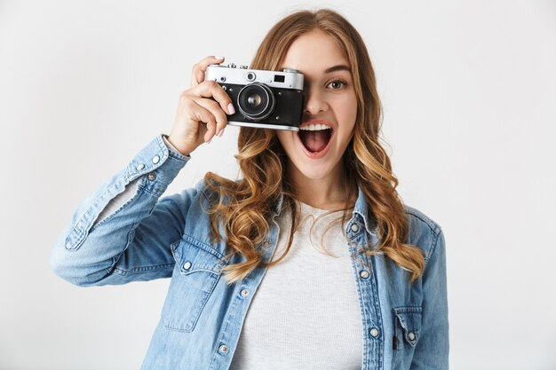 Attractive young girl standing isolated over white , taking a picture with photo camera