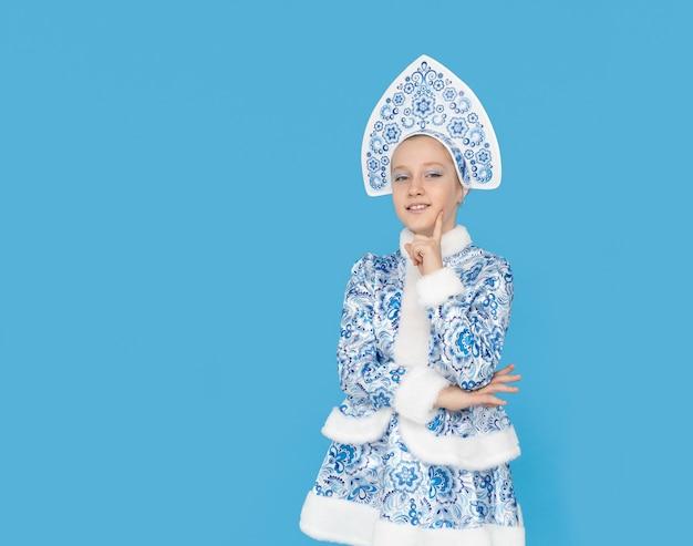 Привлекательная молодая девушка в синем костюме снегурочки улыбается. изолированные на синей стене