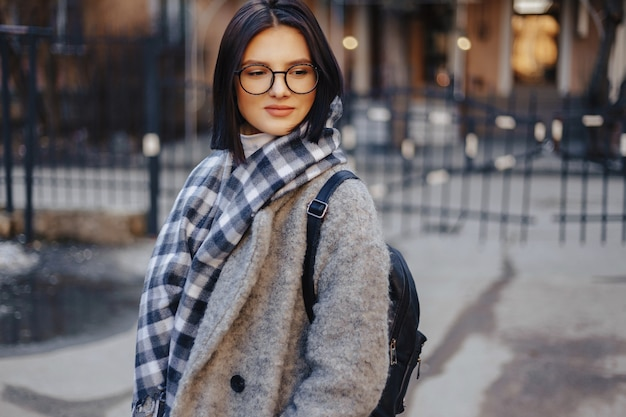 Attractive young girl wearing glasses in a coat walking on a sunny day