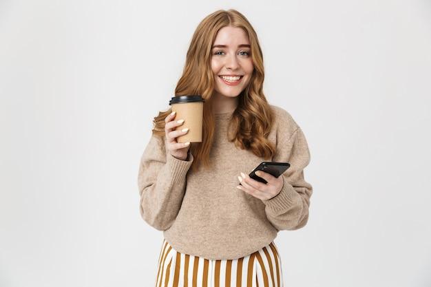 Привлекательная молодая девушка в свитере, стоящая изолированно над белой стеной, пьет кофе на вынос во время использования мобильного телефона