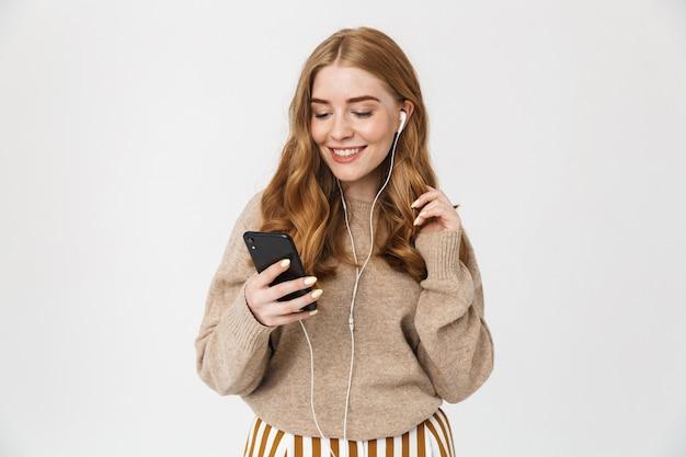 白い壁の上に孤立して立っているセーターを着て、イヤホンで音楽を聴いて、携帯電話を持って魅力的な若い女の子