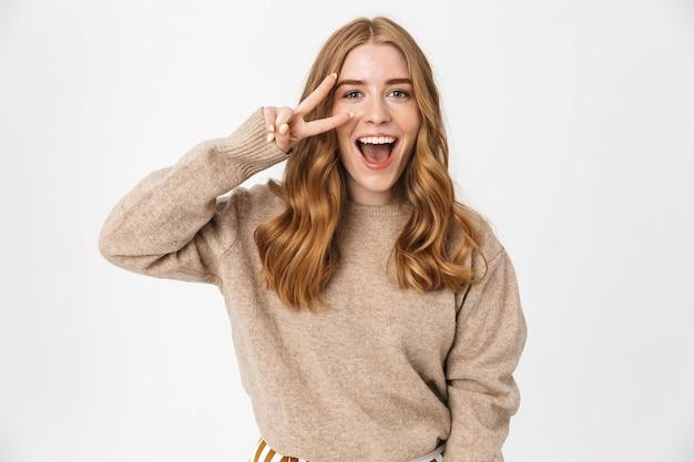 흰 벽, 평화 제스처 위에 고립 된 스웨터를 입고 매력적인 젊은 여자