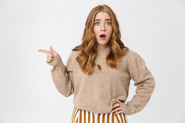 Привлекательная молодая девушка в свитере стоит изолированно над белой стеной, указывая на пространство для копирования