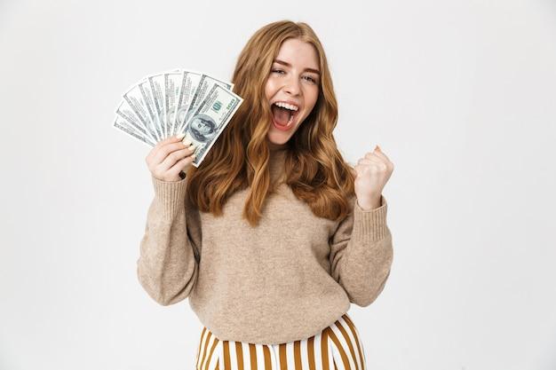 스웨터를 입은 매력적인 어린 소녀가 흰 벽 위에 고립되어 서서 돈 지폐를 보여주며 축하하고 있다