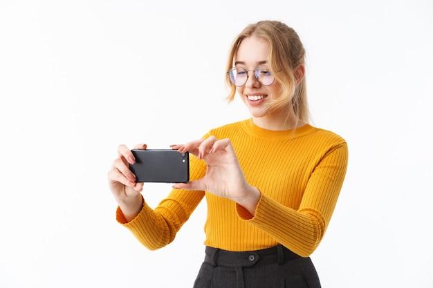 白い壁の上に孤立して立っているセーターを着て、携帯電話で写真を撮る魅力的な若い女の子