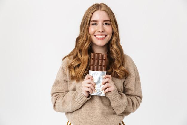 Привлекательная молодая девушка в свитере стоя изолирована над белой стеной