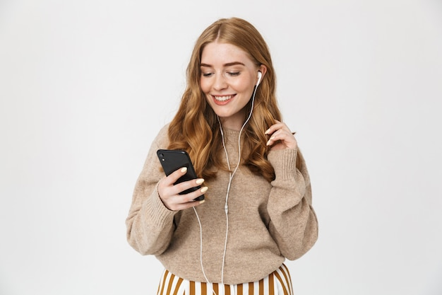 Attractive young girl wearing sweater standing isolated over white wall, listening to music with earphones, holding mobile phone