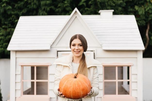 彼女の手にカボチャを持つ魅力的な若い女の子、秋、ハロウィーン