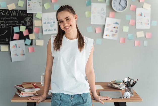 웃 고, 스티커와 함께 회색 벽에 테이블에 기대어 꼬리와 매력적이 고 어린 소녀.