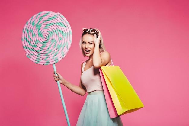 거대한 달콤한 막대 사탕으로 서있는 상단과 치마를 입고 금발 머리를 가진 매력적인 어린 소녀