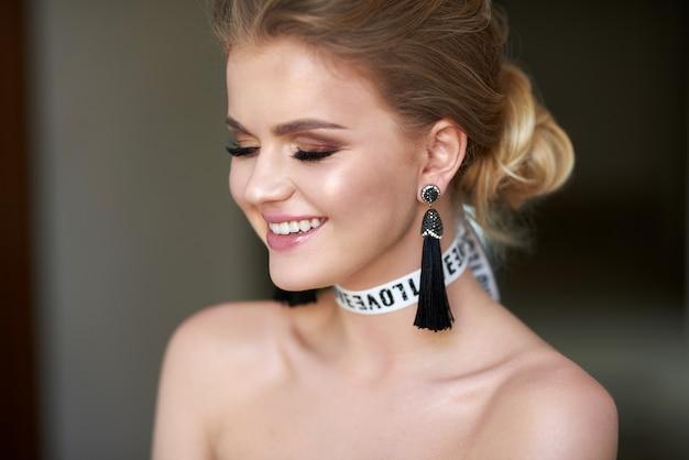 集めた髪を持つ魅力的な若い女の子。灰色の壁に完璧な肌を持つブロンドの女の子の写真