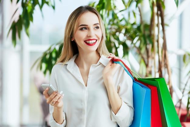 白いブラウスを着て、カラフルな買い物袋を持って立って、携帯電話を持って、ショッピングのコンセプトを明るい茶色の髪と赤い唇を持つ魅力的な若い女の子。