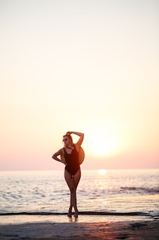 Attractive young girl with long hair poses in front of the camera on the beach. she is wearing a black swimsuit. golden sunset light