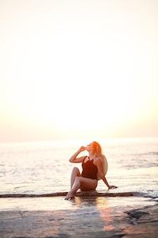 ビーチのカメラの前でポーズをとる長い髪の魅力的な若い女の子。彼女は黒い水着を着ています。黄金の夕日の光