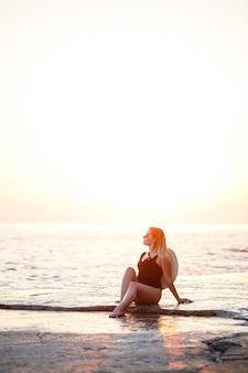 長い髪の魅力的な若い女の子がビーチでポーズをとる。彼女は黒い水着を着ています。黄金の夕日の光