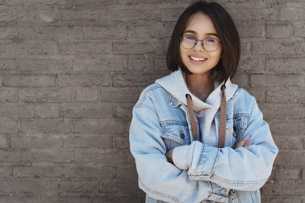 짧은 머리, 안경 및 거리 스타일 옷을 입고, 벽돌 벽에 기대어 매력적인 젊은 여자.