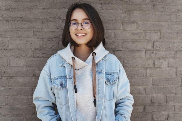 Attraente ragazza giovane con i capelli corti, con gli occhiali e vestiti in stile street, appoggiato su un muro di mattoni.