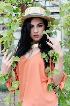 Привлекательная молодая девушка с волнистыми волосами в шляпе и стильном наряде позирует возле виноградной лозы