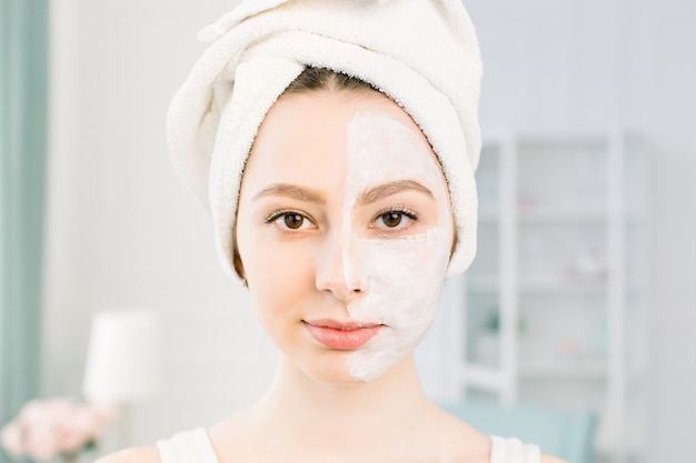 An attractive young girl with a white towel on her head applied a useful clay mask to half the face