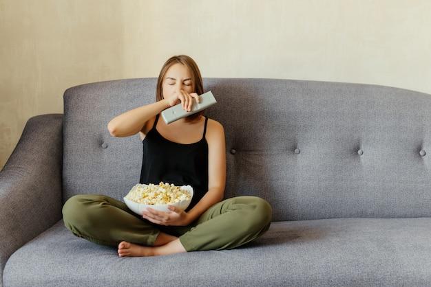 灰色のソファーに座って、テレビを見ながらポップコーンを食べながらあくびをして魅力的な若い女の子。家に