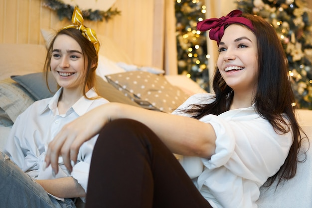 Attractive young girlfriends in stylish clothes sitting together on floor discussing latest news