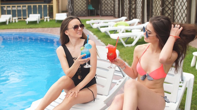 Attractive young girlfriends in swimsuits rest by the pool with cats in their hands