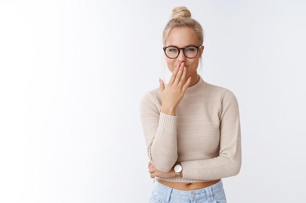매력적인 젊은 글래머 소녀는 흰색 배경 위에 포즈를 취하면서 손바닥을 숨기고 낄낄대며 웃으면서 웃고 있는 동료를 보며 킥킥 웃는다.
