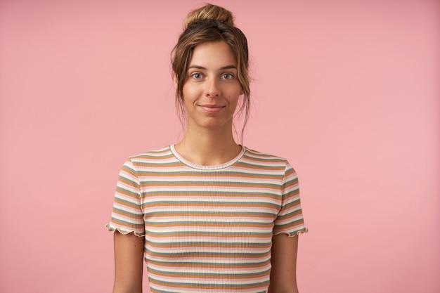 Attraente giovane donna bruna dagli occhi verdi che sorride delicatamente mentre guarda positivamente la fotocamera, tenendo le mani abbassate mentre si trova su sfondo rosa