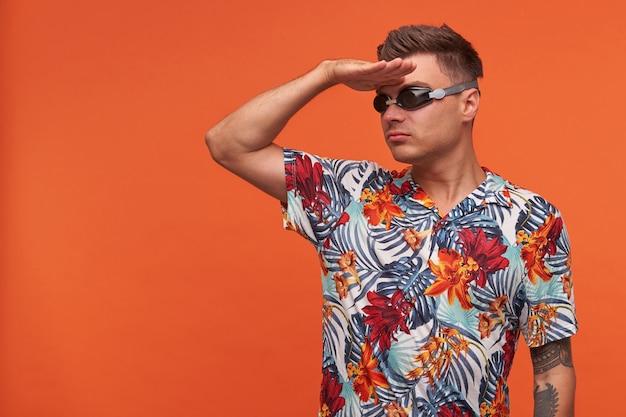 船長のようなポーズをとる魅力的な若い男、パトロールジェスチャーをする、手のひらを額に上げる、水泳用メガネと花柄のシャツを着る