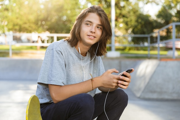 Attractive young guy spending time at the skate park, listening to music with earphones