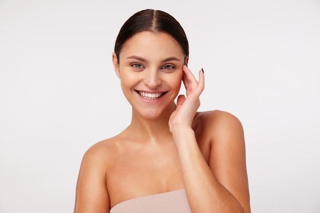 Привлекательная молодая счастливая брюнетка женщина с естественным макияжем, носящая прическу «конский хвост», стоя, весело улыбаясь и трогая ее лицо поднятой рукой
