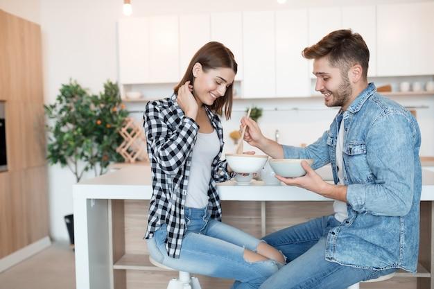 Привлекательный молодой счастливый мужчина и женщина на кухне, едят завтрак, пара вместе утром, улыбаясь