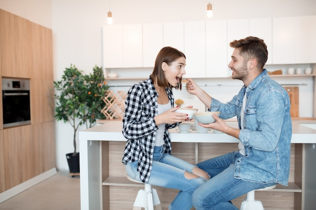 Attractive young happy man and woman in kitchen, eating breakfast, couple together in morning, smiling